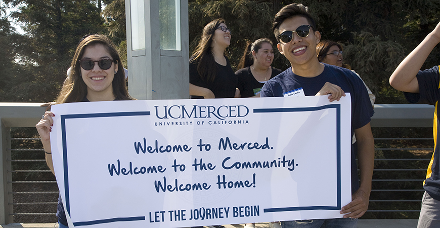 "Two UC Merced students hold a sign that reads: ""Welcome to Merced, welcome to the community, welcome home!"""